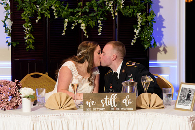 Bride and groom toasting and a kiss at the sweetheart table at Testas Banquet Facility in Southington Connecticut