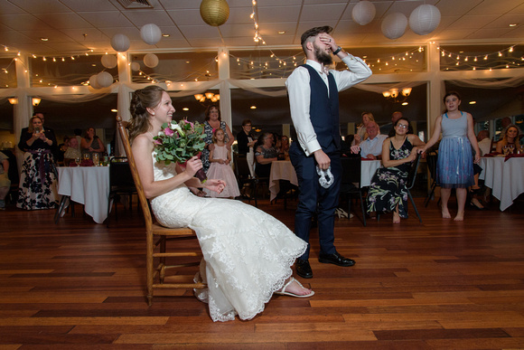 Groom removes the garter during wedding reception at Point Breeze Massachusetts